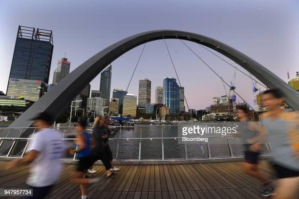 Joggers run past pedestrians on the Horseshoe Bridge in the Elizabeth Quay area of Perth Australia on Wednesday April 11 2018 Australia is scheduled...