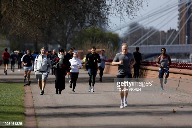 Joggers run to take their exercise in Battersea Park in London on March 28 as life continues in Britain during the novel coronavirus pandemic The two...