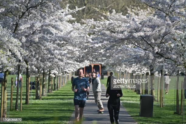 Joggers run under the blossom in Battersea Park in London on March 24 2020 after Britain's government ordered a lockdown to slow the spread of the...