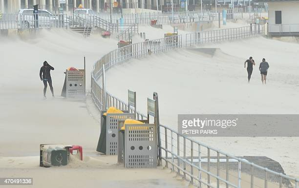 Joggers struggle against sand whipped up by strong winds at Bondi Beach in Sydney on April 21 2015 Sydney and surrounding areas were lashed by wild...