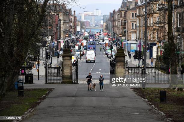 Joggers walk their dog to exercise in Queen's Park Glasgow on March 24 2020 after Britain ordered a lockdown to slow the spread of the novel...
