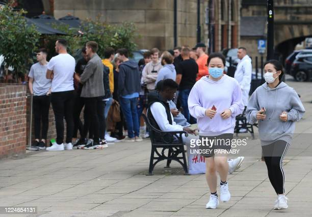 Joggers wearing PPE of a face mask or covering as a precautionary measure against spreading COVID19 run past people queing to enter a reopened pub in...
