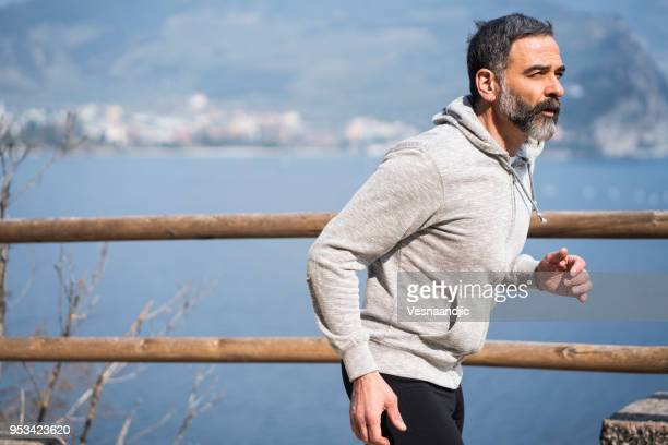 jogging at garda lake - handsome 50 year old men stock photos and pictures