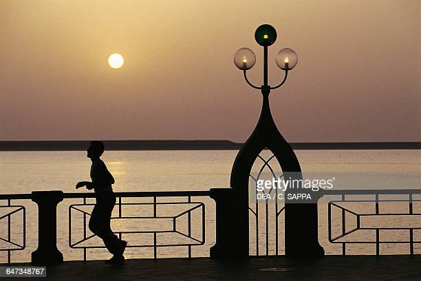 Jogging down the Corniche at sunset the waterfront of Abu Dhabi United Arab Emirates
