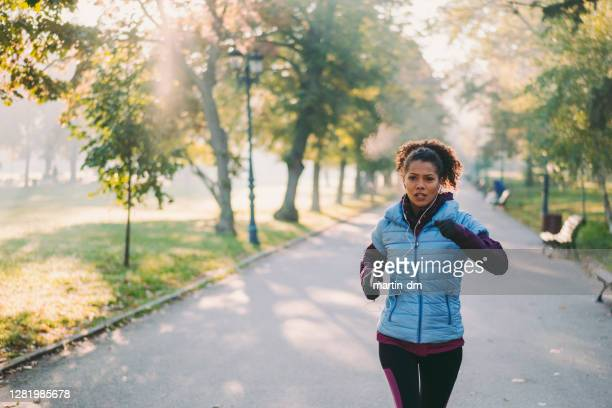 jogging in autumn park - cardiovascular exercise stock pictures, royalty-free photos & images