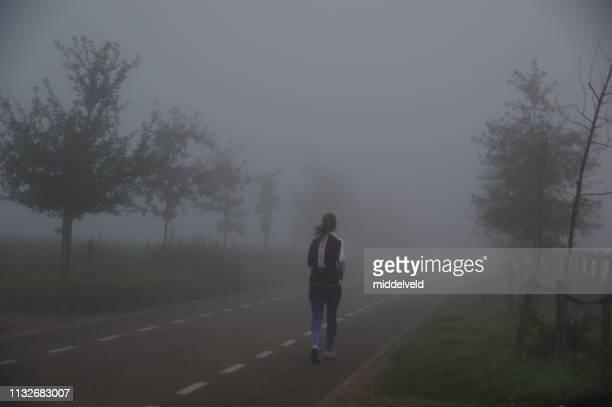 joggen im nebel - sports round stock-fotos und bilder