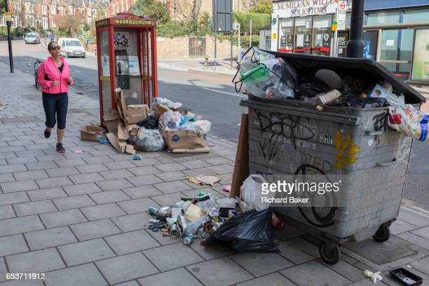 A jogging lady runs past a controversial local issue of discarded rubbish and flytipped litter on the street on 7th March 2017 in Herne Hill SE24...