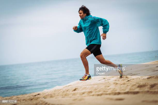Jogging near the sea shore -  strong man running in the sand