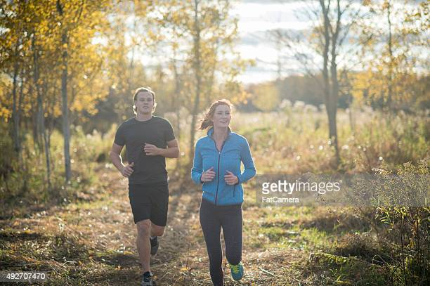 jogging on a fall day - community engagement stock pictures, royalty-free photos & images