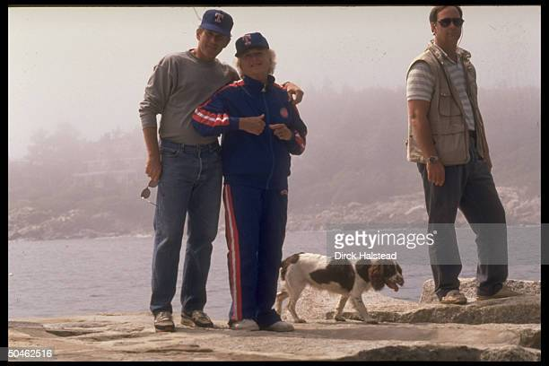 Jogging suit cap clad Barbara Bush in affectionate stance w her son George w family dog Millie secret serviceman in tow