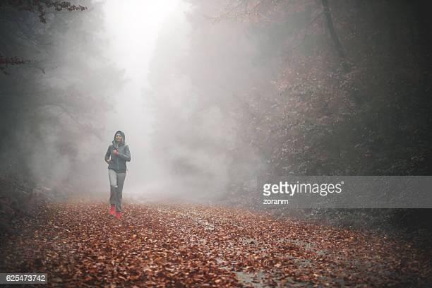 Jogging through foggy forest