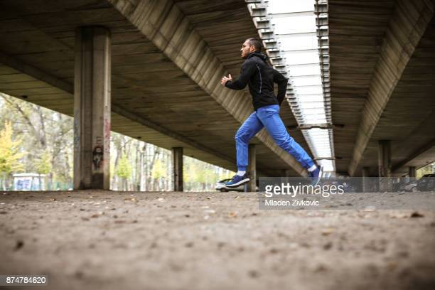 jogging under bridge. - one young man only stock pictures, royalty-free photos & images