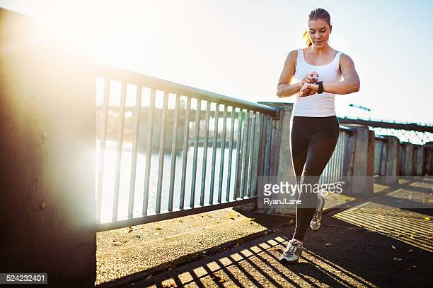 jogging woman checks smart watch - checking sports stock pictures, royalty-free photos & images