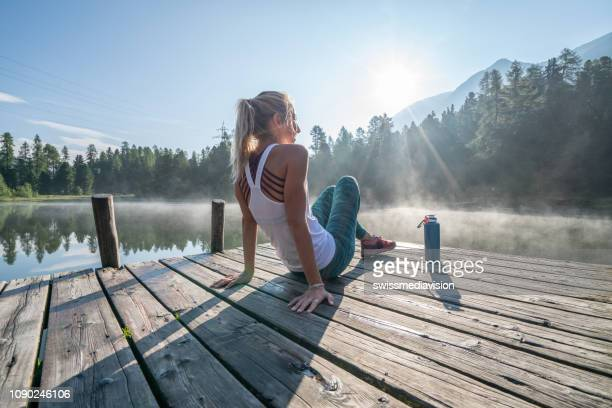 jogging woman relaxing on lake pier at sunrise enjoying freshness from nature - wellbeing stock pictures, royalty-free photos & images