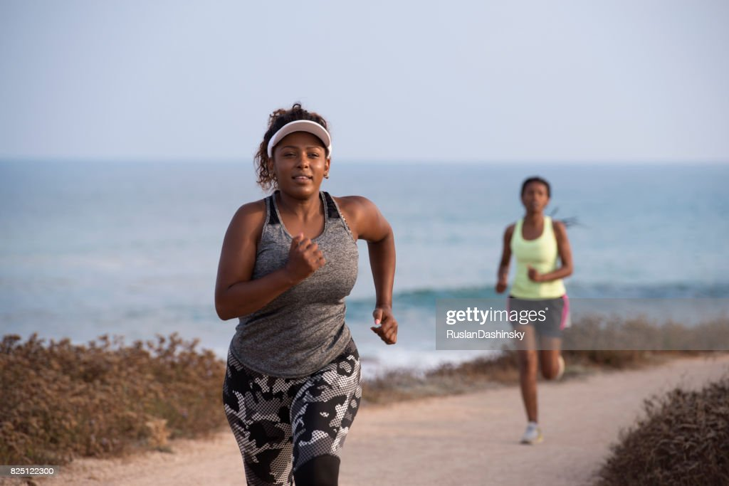 Jogging women running. Beginner plump woman and female pro runner during an outdoor workout on the coast line. : Stock Photo