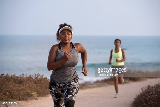 Jogging women running. Beginner plump woman and female pro runner during an outdoor workout on the coast line.