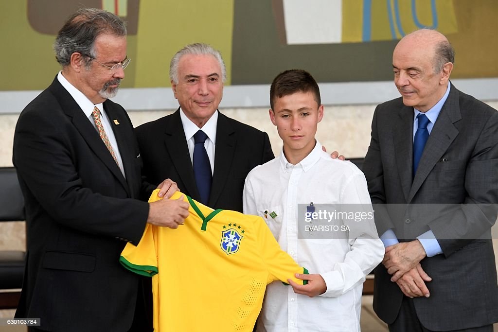 Johan Alexis Ramirez (2-R), a 15-year-old Colombian boy who was one of the first to arrive at the scene of the November 29 LAMIA plane crash in Colombia, poses with Brazilian Defense Minister Raul Jungmann (L), President Michel Temer (2-L) and Foreign Minister Jose Serra (R) during an award ceremony for the Colombians who rescued the victims, at the Planalto Palace in Brasilia on December 16, 2016. The accident killed 71 people and only six survived - four Brazilians and two Bolivians. Among the victims were nearly the entire Chapecoense team from Brazil who were flying to Medellin to play in the finals of the Copa Sudamericana soccer tournament. / AFP / EVARISTO SA
