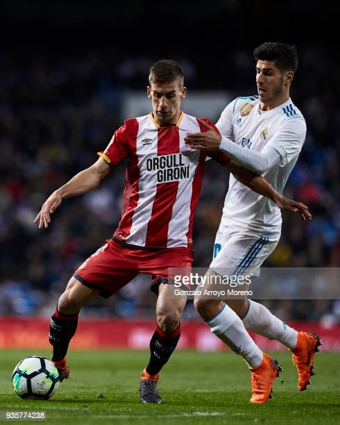 Johan Andres Mojica of Girona FC competes for the ball with Marco Asensio of Real Madrid CF during the La Liga match between Real Madrid CF and...
