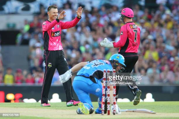Johan Botha and Sam Billings of the Sixers celebrate after dismissing Travis Head of the Strikers during the Big Bash League match between the Sydney...