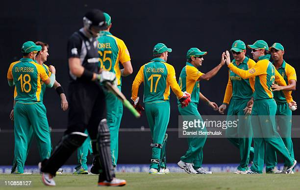 Johan Botha of South Africa celebrates with teammates after taking the catch to dismiss of Martin Guptill of New Zealand off the bowling of Robin...