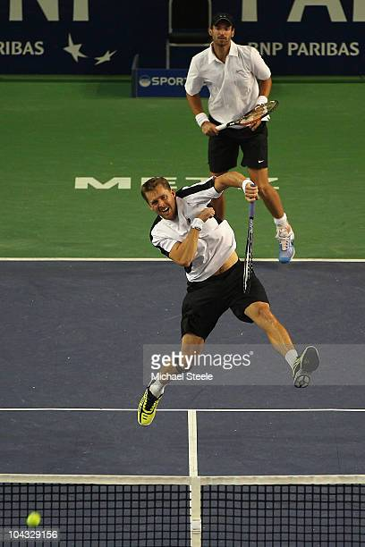 Johan Brunstrom of Sweden smashes a volley as doubles partner Christopher Kas of Germany looks on during their match against Richard Gasquet and...