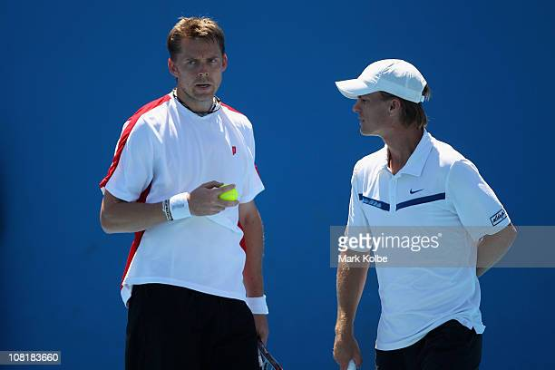 Johan Brunstrom of Sweden talks tactics with partner Stephen Huss of Australia in their first round doubles match against Lukasz Kubot of Poland and...