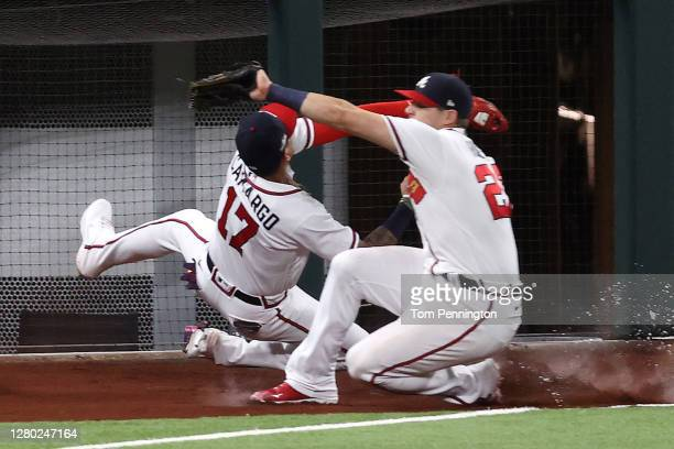 Johan Camargo of the Atlanta Braves catches a fly ball as Austin Riley slides past him against the Los Angeles Dodgers during the sixth inning in...
