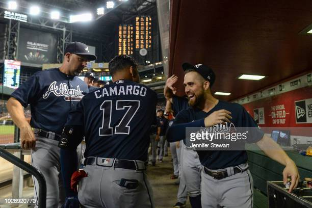 Johan Camargo of the Atlanta Braves celebrates in the dugout with Ender Inciarte after hitting a solo home run in the third inning of the MLB game...