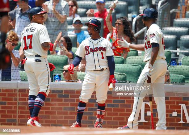 Johan Camargo of the Atlanta Braves celebrates scoring a run with teammates Ozzie Albies and Julio Teheran in the third inning of an MLB game against...