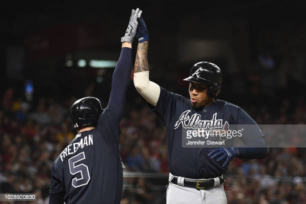 Johan Camargo of the Atlanta Braves is congratulated by Freddie Freeman after hitting a solo home run in the third inning of the MLB game against the...