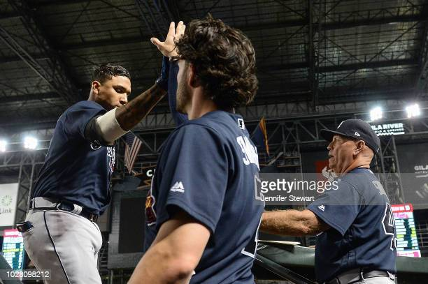 Johan Camargo of the Atlanta Braves is congratulated by manager Brian Snitker and Dansby Swanson after hitting a solo home run in the sixth inning of...