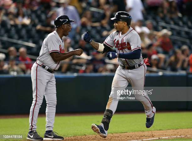 Johan Camargo of the Atlanta Braves is congratulated by third base coach Ron Washington after hitting a tworun home run against the Arizona...