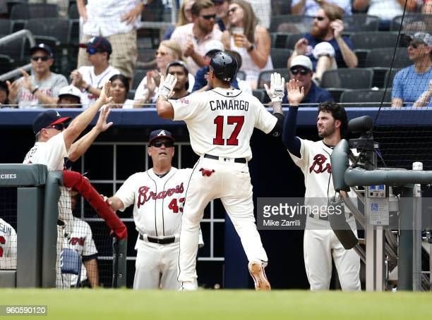 Johan Camargo of the Atlanta Braves is congratulated in the dugout after scoring in the seventh inning during the game against the Miami Marlins at...