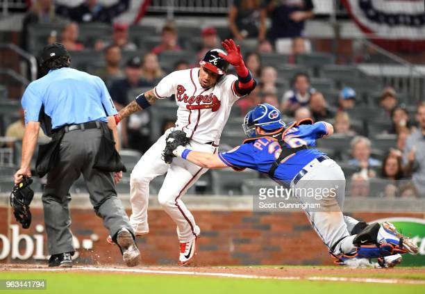 Johan Camargo of the Atlanta Braves is tagged out at home plate by Kevin Plawecki of the New York Mets during the second inning at SunTrust Field on...