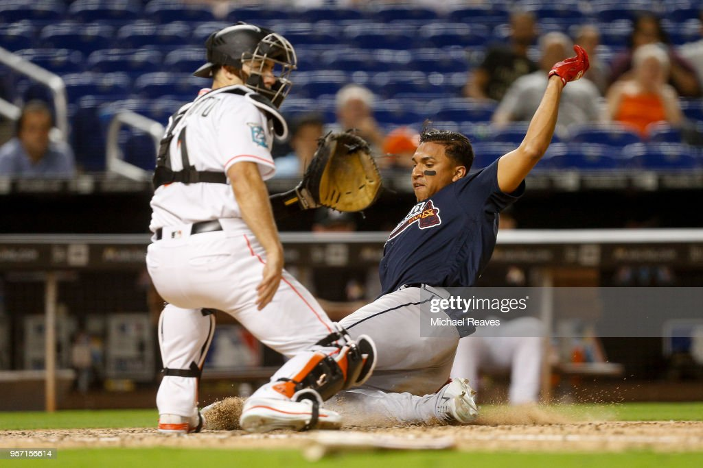 Johan Camargo #17 of the Atlanta Braves slides safely around J.T. Realmuto #11 of the Miami Marlins tag in the ninth inning at Marlins Park on May 10, 2018 in Miami, Florida.