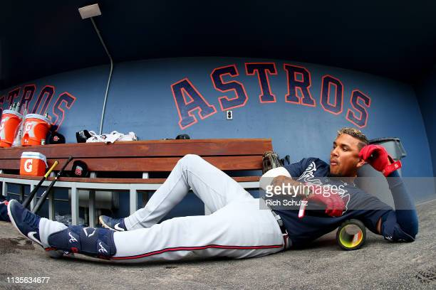 Johan Camargo of the Atlanta Braves stretches on a roller in the dugout during of a spring training baseball game against the Washington Nationals at...