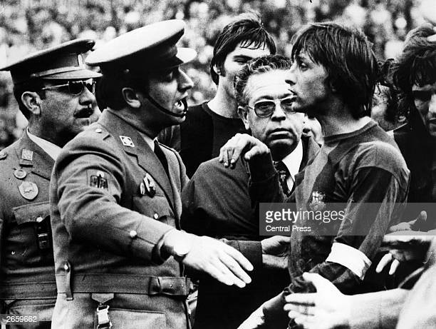 Johan Cruyff, captain of Barcelona, is escorted off the field by police during the Barcelona Vs Malaga match in Malaga, for repeatedly opposing the...