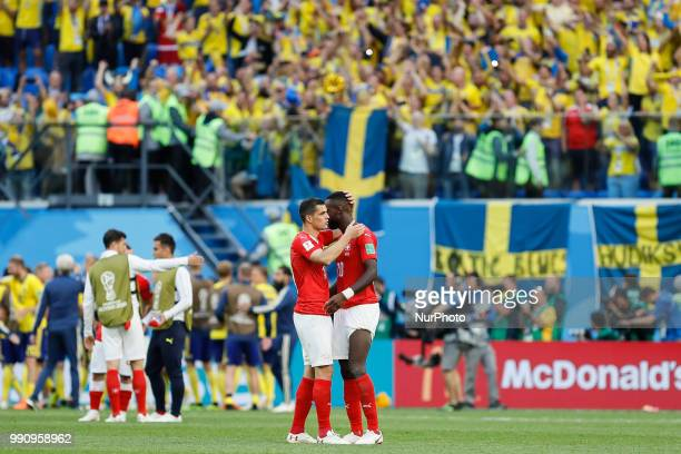Johan Djourou and Granit Xhaka of Switzerland national team comfort each other after their team defeat during the 2018 FIFA World Cup Russia Round of...