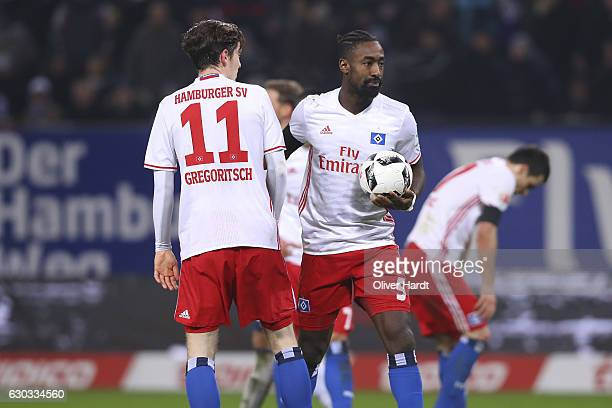 Johan Djourou and Michael Gregoritsch of Hamburg speaks during the Bundesliga match between Hamburger SV and FC Schalke 04 at Volksparkstadion on...