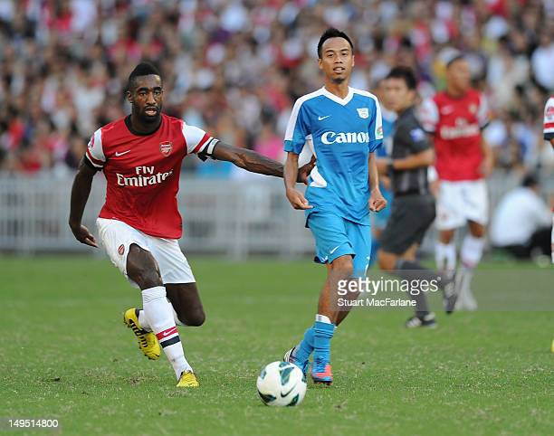 Johan Djourou of Arsenal breaks past Cheng Sui Wai of Kitchee during the pre-season Asian Tour friendly match between Kitchee FC and Arsenal at Hong...