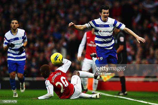 Johan Djourou of Arsenal slides in to tackle Joey Barton of Queens Park Rangers during the Barclays Premier League match between Arsenal and Queens...