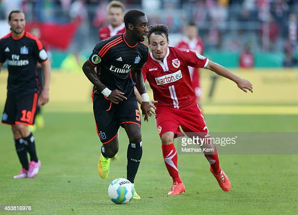 Johan Djourou of Hamburg battles for the ball with Robert Berger of Cottbus during the DFB Cup match between FC Energie Cottbus and Hamburger SV at...