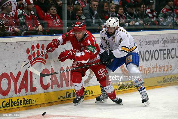 Johan Ejdepalm of EHC Muenchen uses his stick against Jason Jaspers of Koelner Haie during the DEL match between Koelner Haie and EHC Muenchen at...