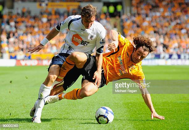 Johan Elmander of Bolton is tackled by Stephen Hunt of Hull during the Barclays Premier League match between Hull City and Bolton Wanderers at the KC...