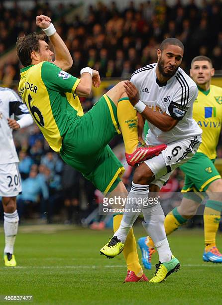 Johan Elmander of Norwich seems to make contact with Swansea City's Ashley Williams' groin area as they clash when they go for the ball during the...