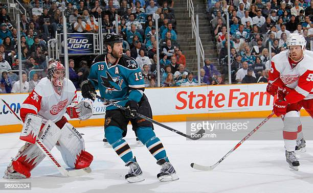 Johan Franzen and Jimmy Howard of the Detroit Red Wings follow the puck while Joe Thornton of the San Jose Sharks looks on in Game Five of the...