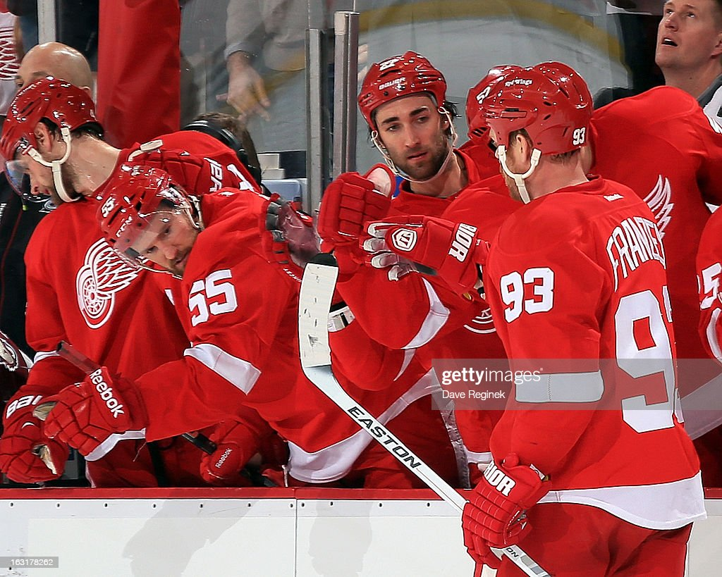 Johan Franzen #93 of the Detroit Red Wings celebrates with teamates Kyle Quincy #27 and Niklas Kronwall #55 after scoring a goal in a NHL game against the Colorado Avalanche at Joe Louis Arena on March 5, 2013 in Detroit, Michigan.