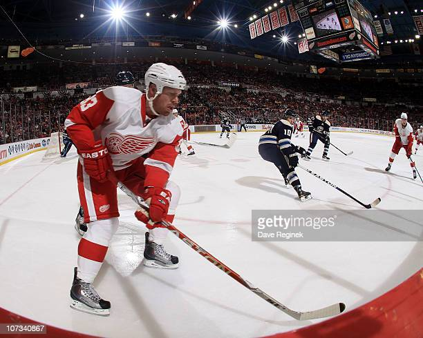 Johan Franzen of the Detroit Red Wings digs the puck out of the corner during an NHL game against the Columbus Blue Jackets at Joe Louis Arena on...