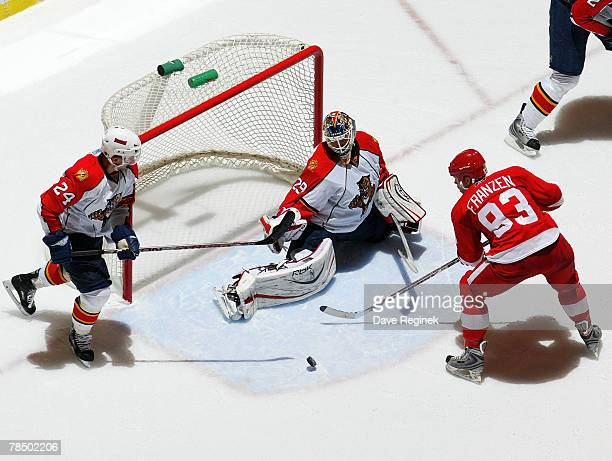 Johan Franzen of the Detroit Red Wings shoots the puck on goalie Tomas Vokoun of the Florida Panthers during a NHL game at Joe Louis Arena December...