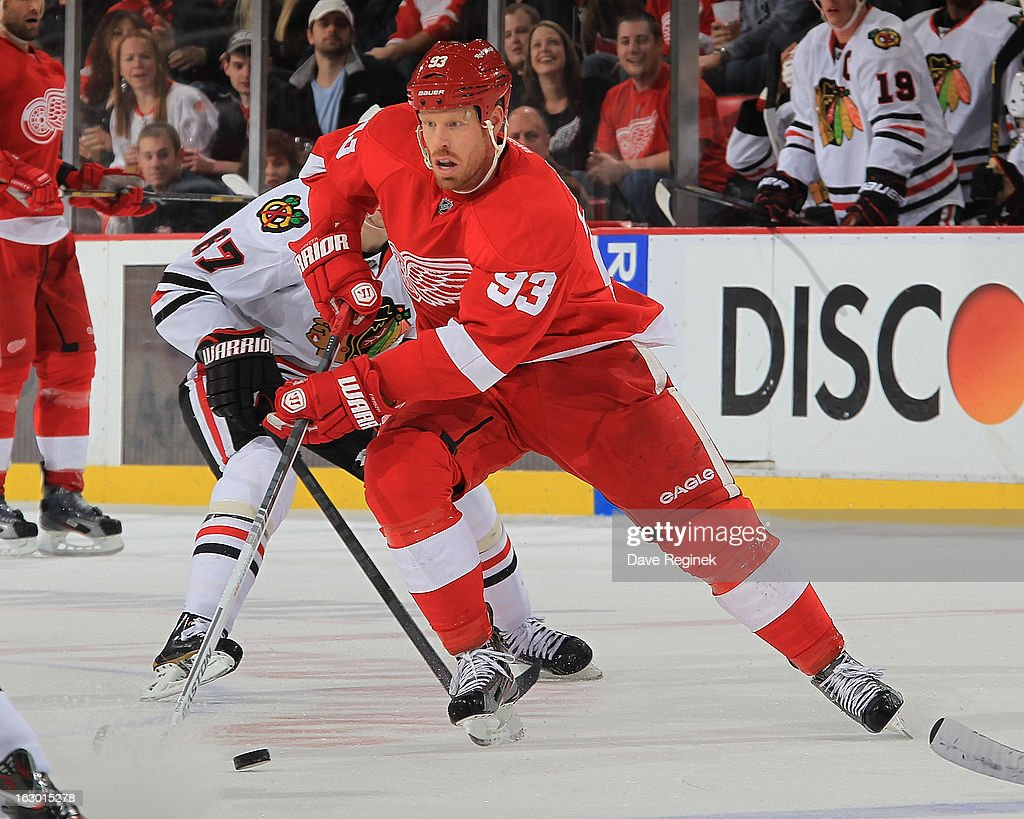Johan Franzen #93 of the Detroit Red Wings skates up ice with the puck during an NHL game against the Chicago Blackhawks at Joe Louis Arena on March 3, 2013 in Detroit, Michigan.